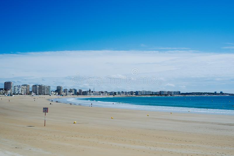 beautiful bay with a stunning blue sea white yellow sand and nice cityscape stock images
