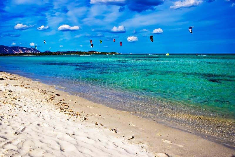 Beautiful beach. Kitesurfers in the Tyrrhenian Sea near la Cinta beach, Sardinia, Italy stock photography
