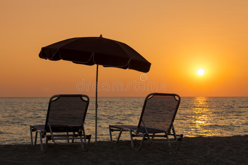 Beautiful beach with deck chairs and parasol at sunset.  royalty free stock photos