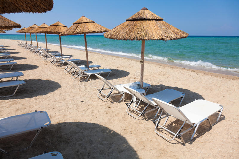 Beautiful beach with deck chairs and umbrellas. On the sandy beach in Nea Irakleia (Halkidiki). Thessaloniki - Greece stock photo