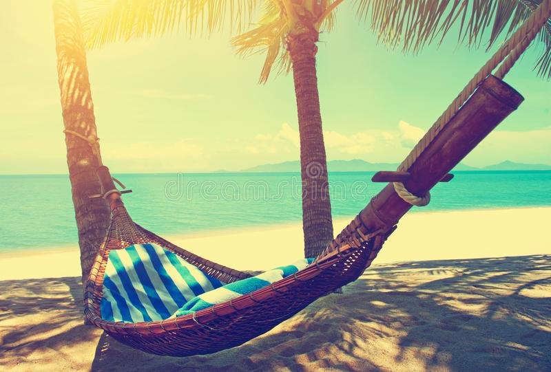 Beautiful beach. Hammock between two palm trees on the beach. Holiday and vacation concept. Tropical beach. Beautiful tropical isl stock photo