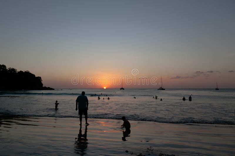 Beautiful beach kata phuket in thailand on puhket island. Silhouettes of people at sunset. In the foreground are the silhouette of. A man and a child stock image
