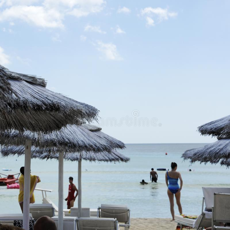 Beautiful beach resort with white straw umbrellas on a blue sky and white clouds. On the background some people having fun on the stock photography
