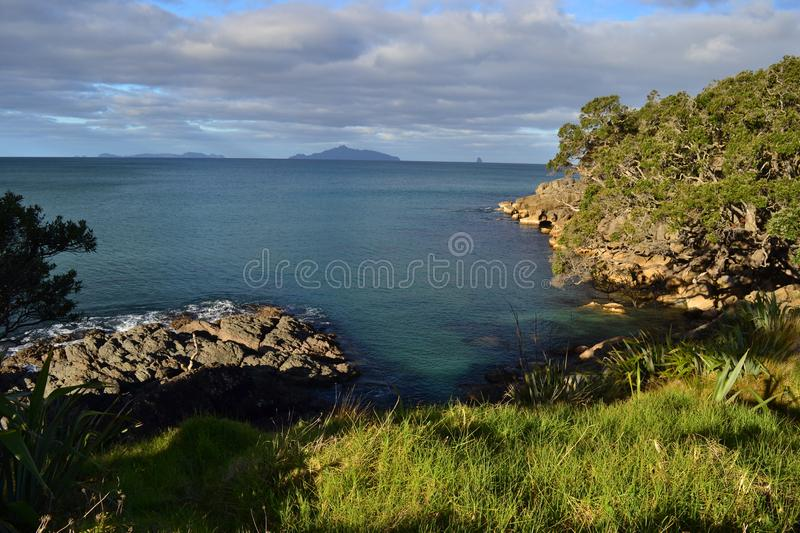 Waipu beach, cove, Northland, New Zealand. Beautiful beach and seashore in Waipu cove, long beach, remote cliffs, unique landscape with mountains in background stock photos