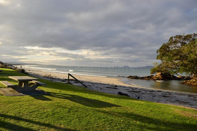 Waipu beach, cove, Northland, New Zealand. Beautiful beach and seashore in Waipu cove, long beach, remote cliffs, unique landscape with mountains in background stock image