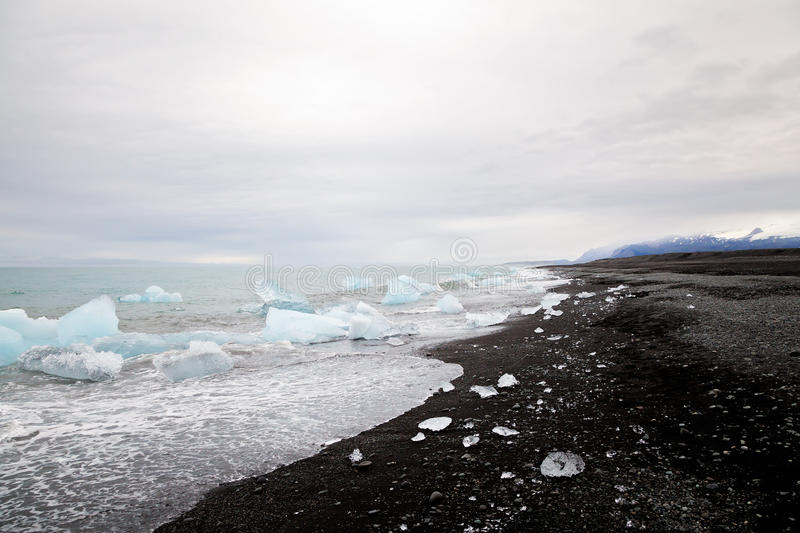Beautiful beach in South Iceland with black lava sand and icebergs from glaciers royalty free stock image