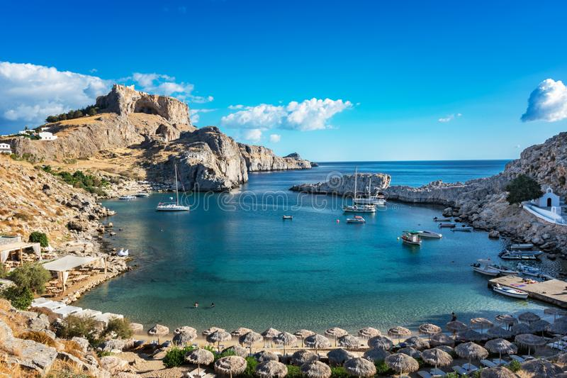 Beautiful beach in St. Paul´s bay, Lindos acropolis in background (Rhodes, Greece) royalty free stock images