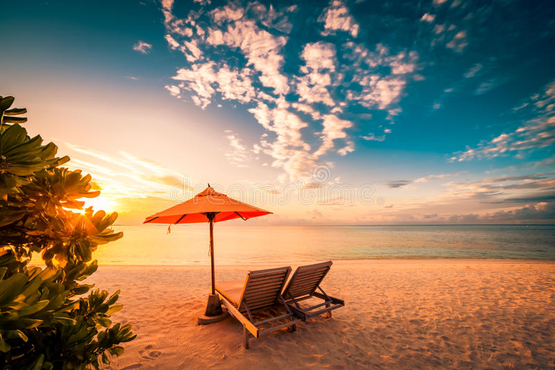 Beautiful beach sunset with sun beds and relaxing mood. Beautiful beach background for summer travel with sun,coconut tree and beach wooden bed on sand with royalty free stock photos