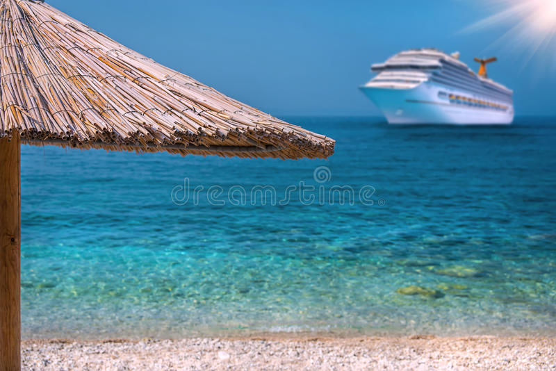 Beautiful Beach with Umbrella. And Cruise Ship royalty free stock photography