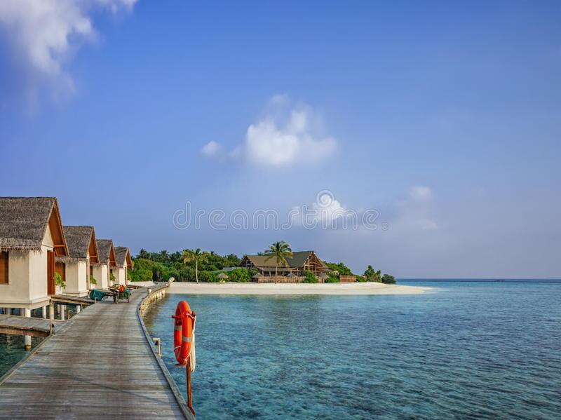Beautiful beach with water bungalows and wooden pier at Maldives royalty free stock images
