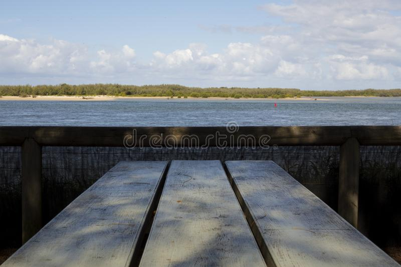 Breakfast Bench Views. Beautiful beach/water views from an outdoor table. Looking over the water to the distant island royalty free stock photography