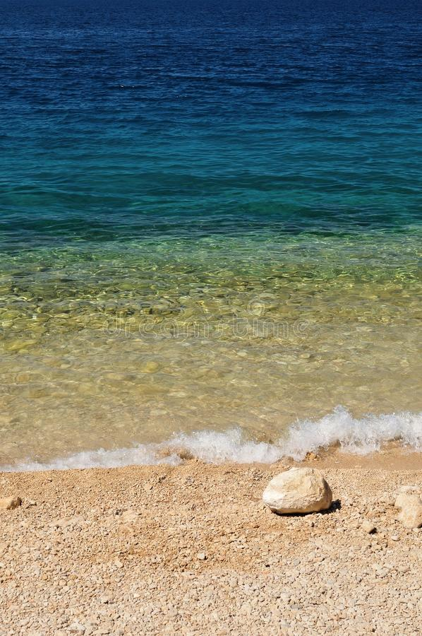 Beautiful beach with wave and big stone royalty free stock image