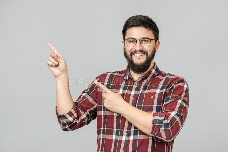 Beautiful bearded guy pointing aside royalty free stock images