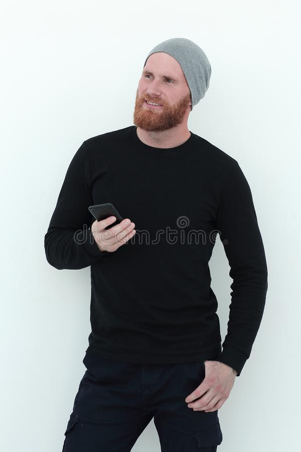 Beautiful bearded man with smartphone looking at blank space stock images