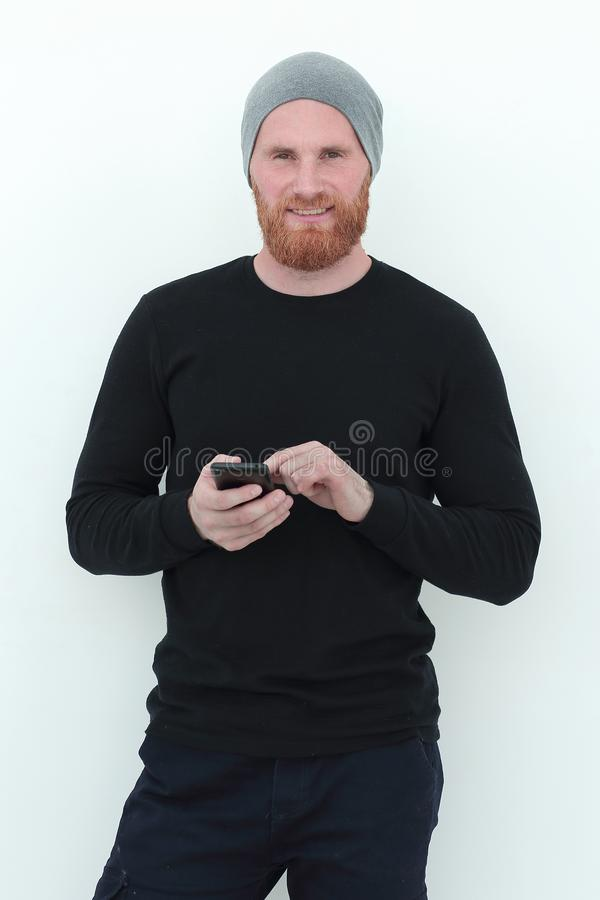 Beautiful bearded man with smartphone looking at blank space stock photo