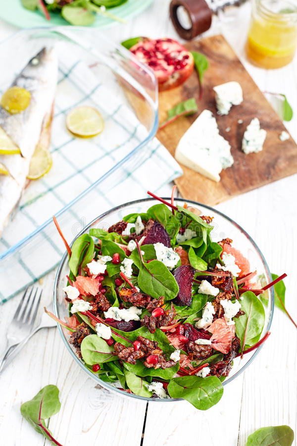 Beautiful beet and spinach Salad. Composition of healthy dinner with beet and baby spinach salad , roasted seabass fish, feta cheese, pomergrat and citrus stock images