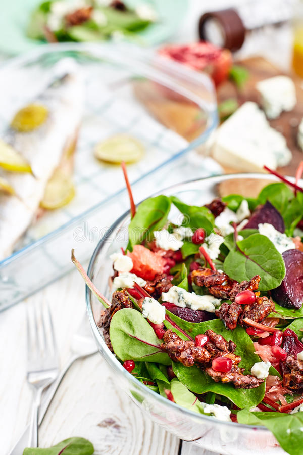 Beautiful beet and spinach Salad. Composition of healthy dinner with beet and baby spinach salad , roasted seabass fish, feta cheese, pomergrat and citrus stock photography