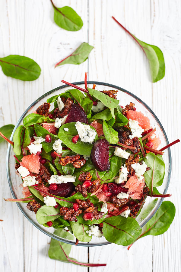 Beautiful beet and spinach Salad. Top view of healthy beet and baby spinach salad with pomergranate, blue cheese Roquefort, gorgonzola grapefruit, caramelized stock images
