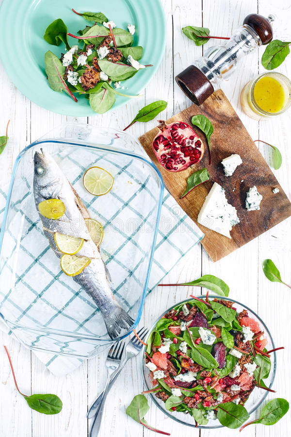 Beautiful beet and spinach Salad. Top view of healthy dinner with beet and baby spinach salad , roasted seabass fish, feta cheese, pomergrat and citrus royalty free stock photos