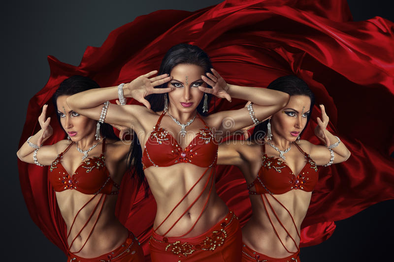 Beautiful belly dancer. Perfoming exotic dance in red flutter dress royalty free stock photography