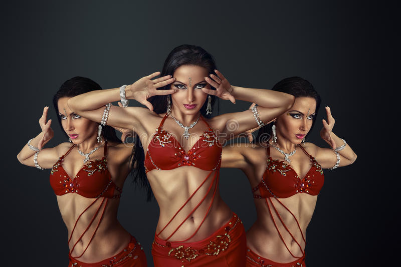 Beautiful belly dancer. Perfoming exotic dance in red flutter dress stock photos