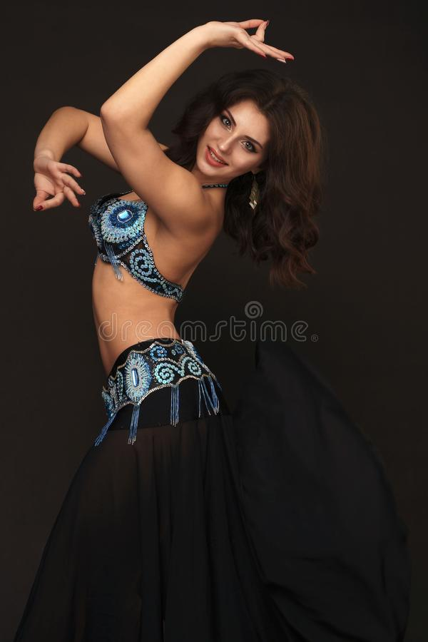Beautiful belly dancer perfoming exotic dance in red flutter dress stock image