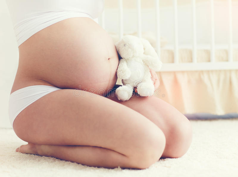 Beautiful belly of pregnant young woman sitting on carpet in nursery room. Beautiful belly of young pregnant young woman sitting on carpet in nursery room royalty free stock image