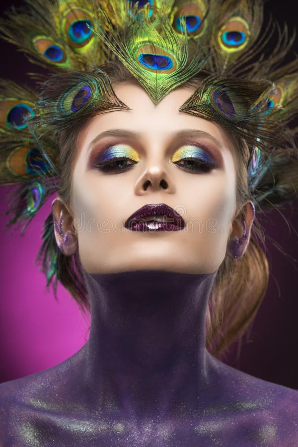 Beautiful big breast girl wearing peacock feathers in her hair a royalty free stock images