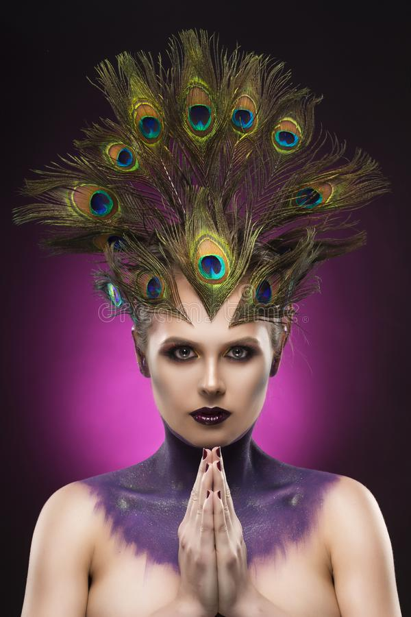 Beautiful big breast girl wearing peacock feathers in her hair a stock photo