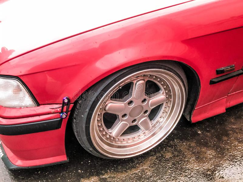 Beautiful big racing wheels of a sports red car with a very low ground clearance on cast shiny expensive alloy wheels in the style royalty free stock photo