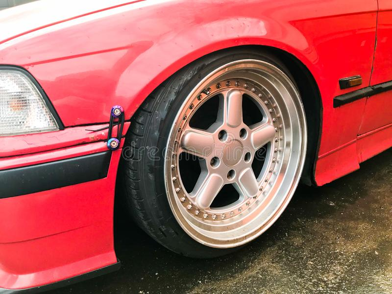 Beautiful big racing wheels of a sports red car with a very low ground clearance on cast shiny expensive alloy wheels in the style stock image