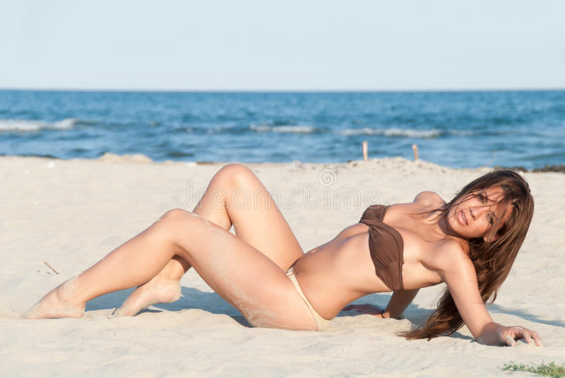 Beautiful bikini model posing on the beach. Wear two pieces swimsuit, attractive body with brunette long hair. Lying on sand on back, full body length. Sea royalty free stock photo