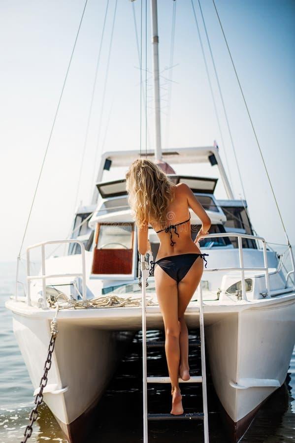 Beautiful bikini woman down the stairs on white yacht stock images