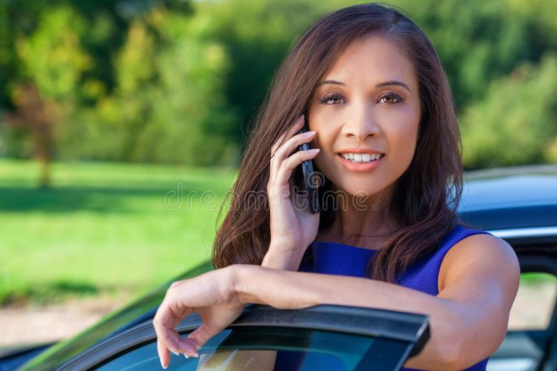 Beautiful Biracial Chinese Asian Eurasian Girl On Cell Phone by Car stock photo