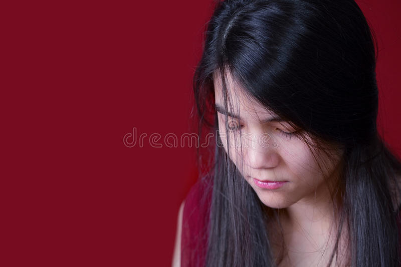 Beautiful, biracial teen girl looking down, depressed or sad, on royalty free stock photo