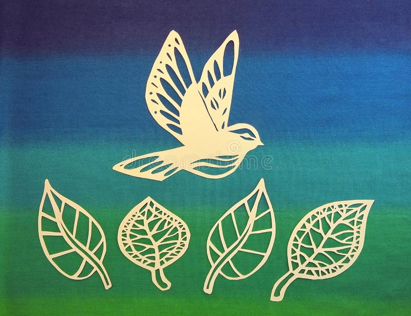 Bird and leaves cut from paper. Beautiful bird and leaves cut from white paper on colorful background stock photos