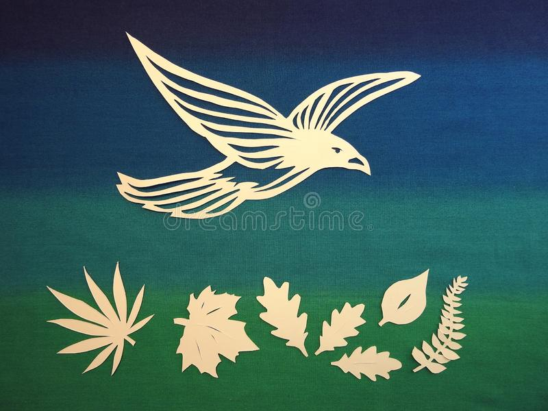 Bird and leaves cut from paper. Beautiful bird and leaves cut from white paper on colorful background stock images