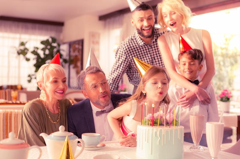 Birthday girl blowing candles while celebrating with family royalty free stock images