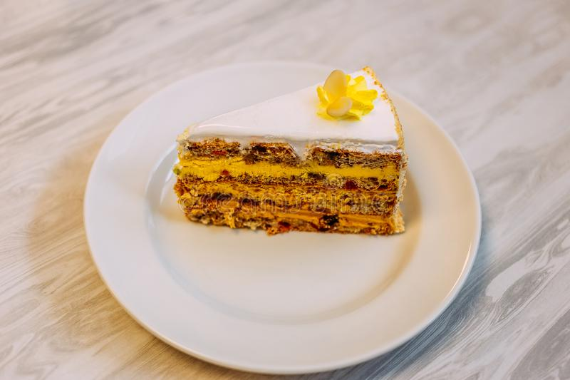 Beautiful biscuit piece of cake with nuts, fruit, cream and protein cream on the table royalty free stock image
