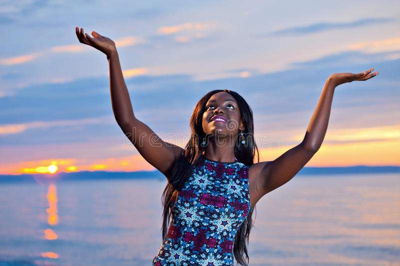 Beautiful black African American woman posing on the beach at sunset. Portrait of beautiful black African American woman posing with open hands up to the sky on royalty free stock photography