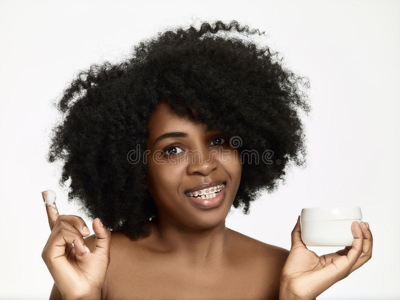 Beautiful black african model with flawless skin smooth complexion applying moisturiser face cream to her cheek. Beauty, cosmetics, skincare concept royalty free stock images