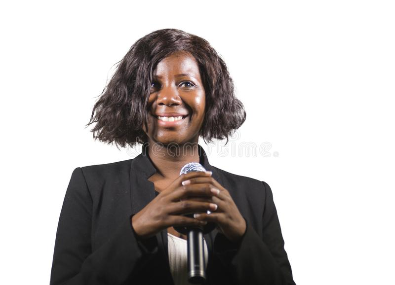 Beautiful black afro American business woman with microphone speaking in auditorium at corporate event or seminar giving stock image