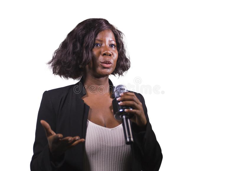 Beautiful black afro American business woman with microphone speaking in auditorium at corporate event or seminar giving. Young attractive and beautiful black stock photos