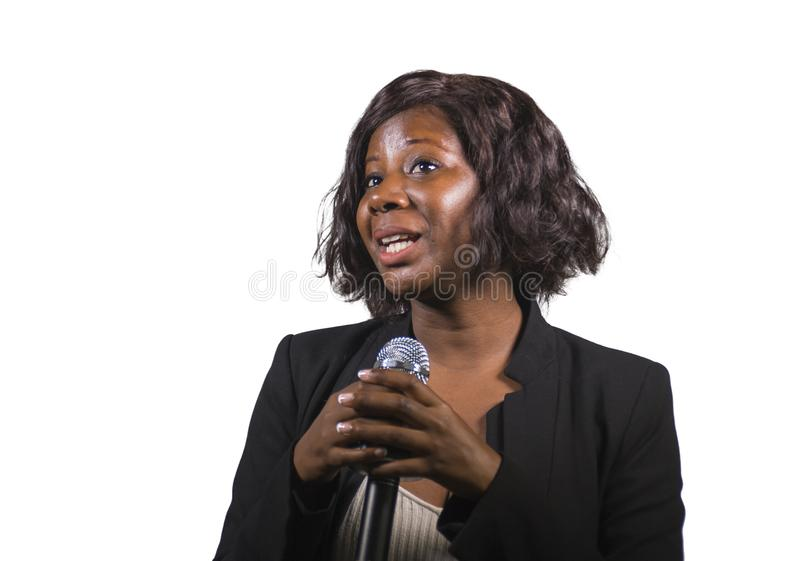 Beautiful black afro American business woman with microphone speaking in auditorium at corporate event or seminar giving. Young attractive and beautiful black stock image