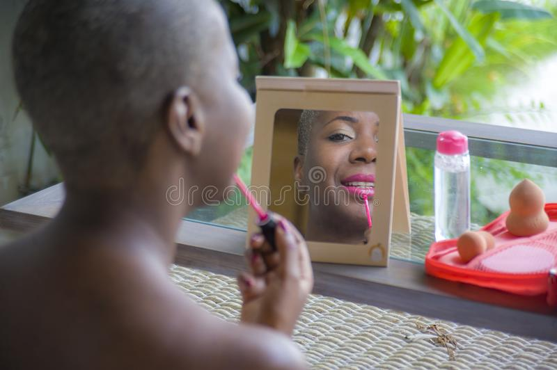Beautiful black afro American woman applying face makeup using brush on her lips looking herself in the mirror at home garden in b royalty free stock photos