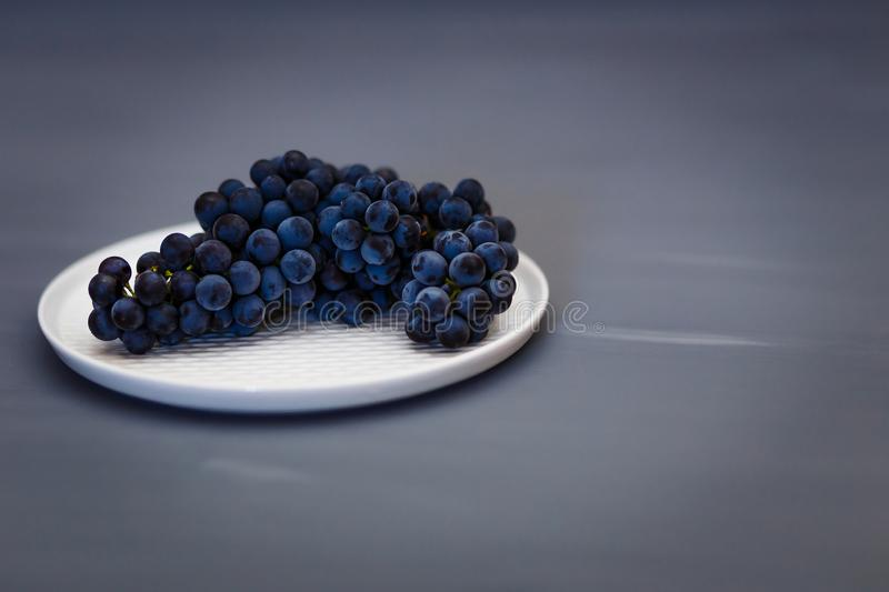 Beautiful black blue grapes Isabella lies on a white plate stock photography