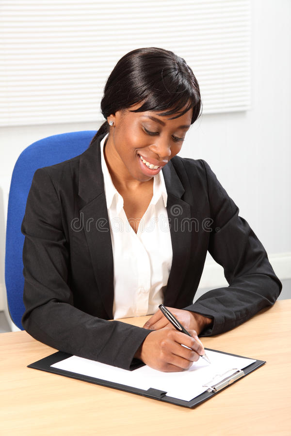 Beautiful black business woman signing document. Happy young black woman working in office sitting to her desk signing a document. She is looking down at the stock photography