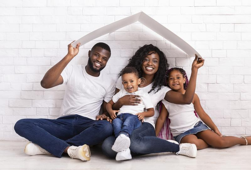 Beautiful Black Family Holding Cardboard Roof Dreaming Of New Home stock photos