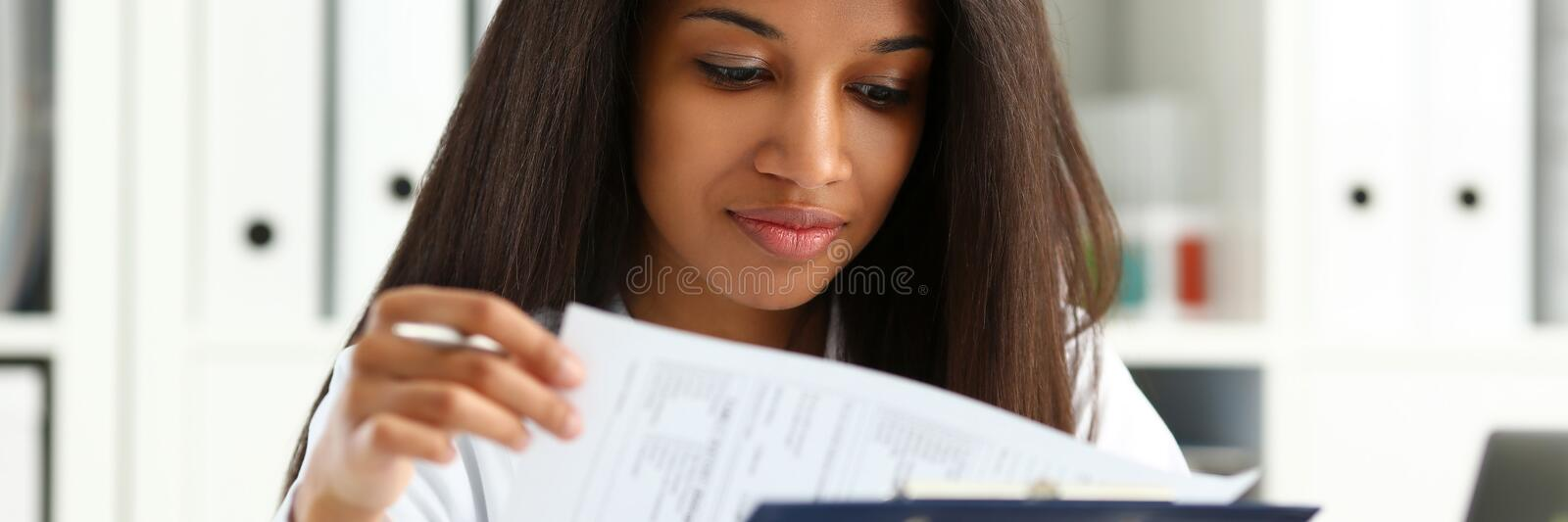 Beautiful black smiling female doctor hold. Clipboard pad and fill something with silver pen. Physical illness prevention prescribe remedy ward round stock photo