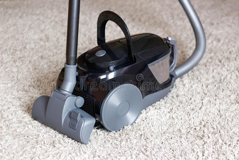 A beautiful black vacuum cleaner stands on a beige carpet with a long pile. Close up stock photography